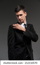 Handsome young man on grey background. Man in black suit removing dirt from shoulder