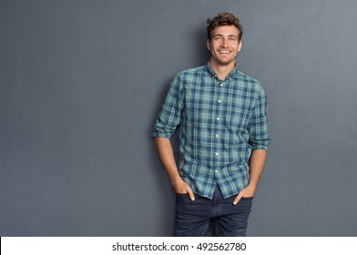 Photo of Handsome young man on grey background looking at camera. Portrait of laughing young man with hands in pockets leaning against grey wall. Happy guy smiling.