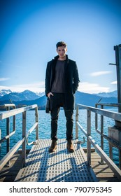 Handsome young man on Luzern lake's shore in a sunny, peaceful day, standing. Switzerland landscape