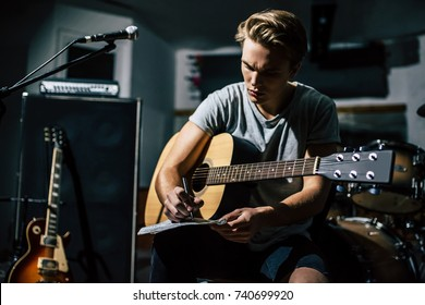 Handsome young man on rehearsal base. Lyric singer with acoustic guitar is writing notes and lyrics in notebook.