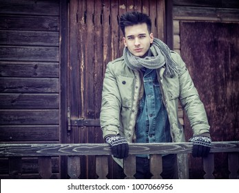Handsome young man in outerwear and scarf posing outside of wooden house looking at camera.