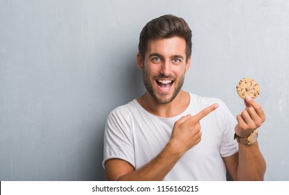 Handsome young man over grey grunge wall eating chocolate chip cooky very happy pointing with hand and finger