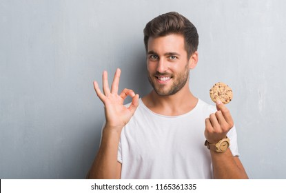 Handsome young man over grey grunge wall eating chocolate chip cooky doing ok sign with fingers, excellent symbol