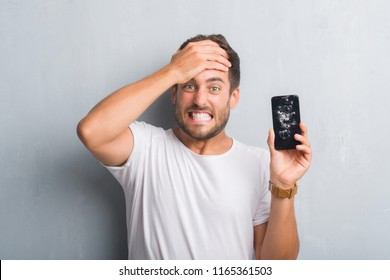 Handsome young man over grey grunge wall showing broken smartphone screen stressed with hand on head, shocked with shame and surprise face, angry and frustrated. Fear and upset for mistake.