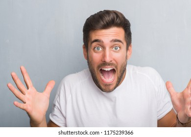 Handsome young man over grey grunge wall very happy and excited, winner expression celebrating victory screaming with big smile and raised hands