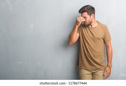 Handsome young man over grey grunge wall tired rubbing nose and eyes feeling fatigue and headache. Stress and frustration concept.