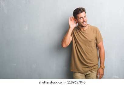 Handsome young man over grey grunge wall smiling with hand over ear listening an hearing to rumor or gossip. Deafness concept.