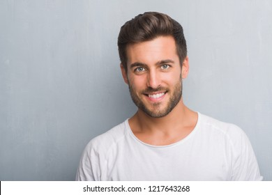 Handsome young man over grey grunge wall with a happy face standing and smiling with a confident smile showing teeth