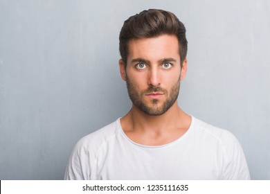 Handsome young man over grey grunge wall with a confident expression on smart face thinking serious