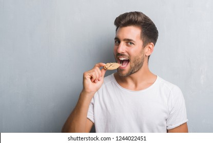 Handsome young man over grey grunge wall eating chocolate chip cooky with a confident expression on smart face thinking serious