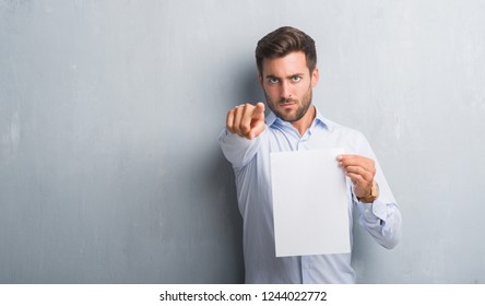 Handsome young man over grey grunge wall holding blank paper sheet contract pointing with finger to the camera and to you, hand sign, positive and confident gesture from the front