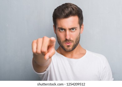 Handsome young man over grey grunge wall pointing with finger to the camera and to you, hand sign, positive and confident gesture from the front