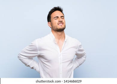 Handsome young man over isolated blue background suffering from backache for having made an effort