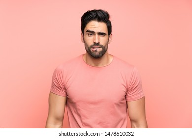 Handsome young man over isolated pink background having doubts and with confuse face expression