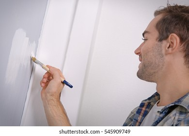 Handsome young man painting wall in room, closeup
