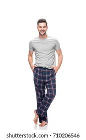 handsome young man in pajamas with hands in pockets isolated on white