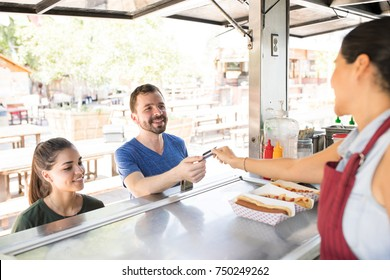 Handsome young man paying for his food with a credit card in a food truck