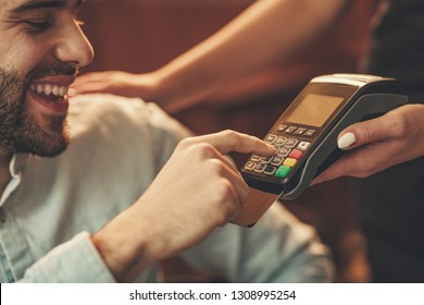 A handsome young man pays to waitress for coffee with credit card in a cafe.