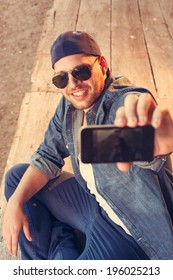 Handsome young man photographing seflie with smart phone