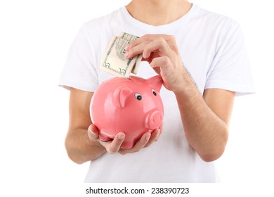 Handsome young man with piggy bank isolated on white