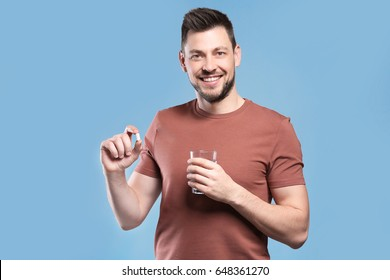 Handsome young man with pill and glass of water on color background