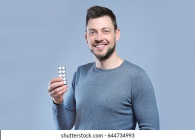 Handsome young man with pills on color background