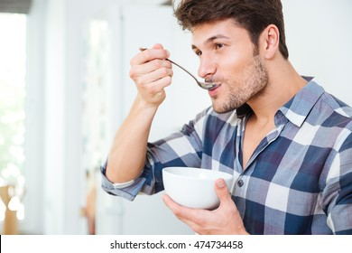 Handsome young man in plaid shirt having breakfast at home