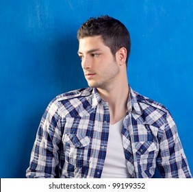 handsome young man with plaid shirt on blue background