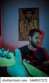 Handsome Young Man Playing Guitar in living room, multicolored neon lights, trendy image