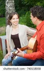 Handsome young man playing guitar and singing to a beautiful woman