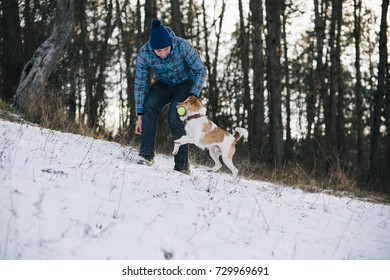 Handsome young man playing with his best friend dog outdoors after first snow.