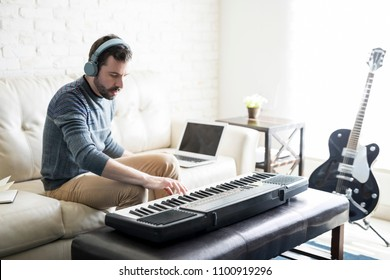 Handsome young man playing music and composing a song with electric piano while sitting in living room at home