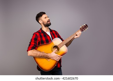 Handsome young man playing on the guitar and singing song