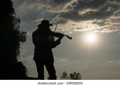 Handsome young man playing the violin very happy. The straw on the farm Warm sunshine.