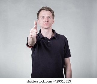 Handsome young man in polo shirt showing ok sign on rey background