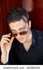 Handsome young man portrait with sunglasses and black shirt
