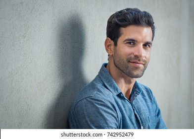 Handsome young man posing on grey background. Portrait of satisfied businessman against grey wall. Close up face of fashionable latin man on grey background.