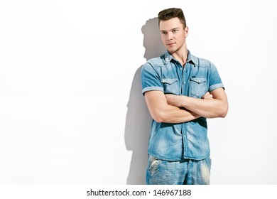 handsome young man posing over white background wearing jeans