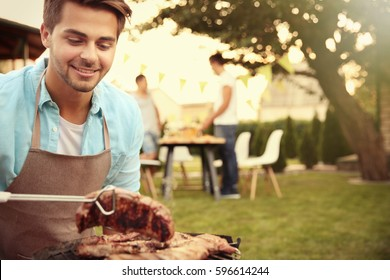 Handsome young man preparing barbecue steaks on grill