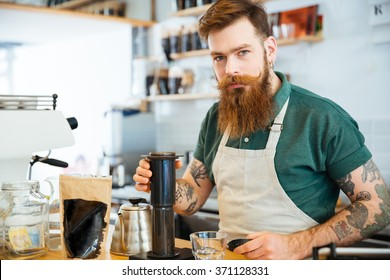 Handsome young man preparing coffee in coffee shop