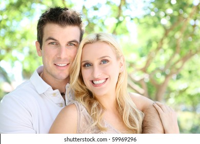 Handsome young man and pretty blonde woman couple in park