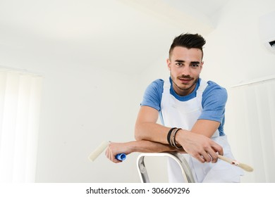 handsome young man professional painter applying white paint in wall with roller