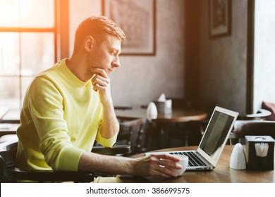 Handsome young man reading the latest news on a laptop while sitting at a table in a cafe