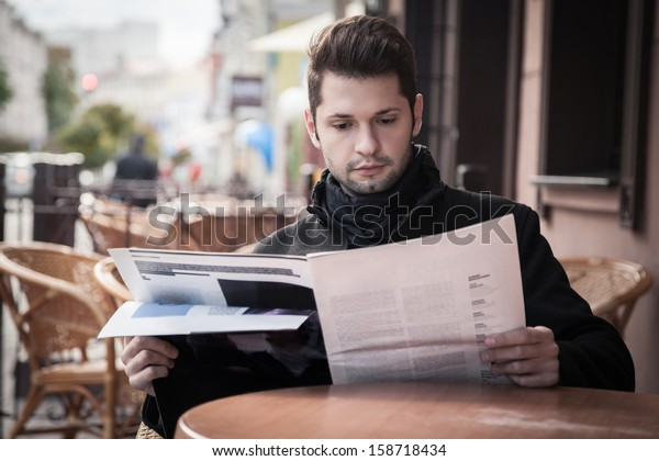 handsome young man reading a magazine in a cafe on the street
