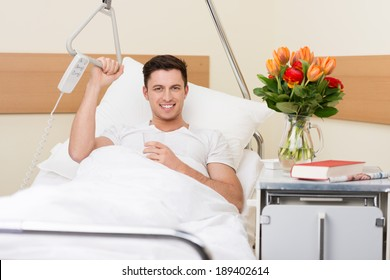 Handsome young man recuperating in a hospital sitting up in bed with a cheerful smile and a big bouquet of flowers on the night stand