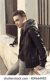 Handsome young man relaxing on street in city, outdoor