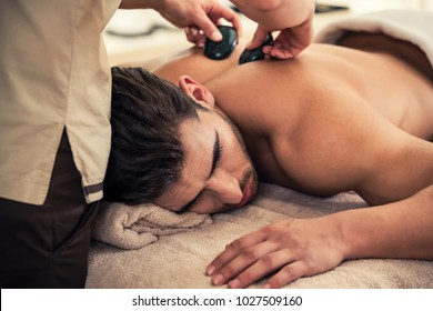 Handsome young man relaxing under the stimulating effect of a traditional hot stone massage at luxury spa and wellness center