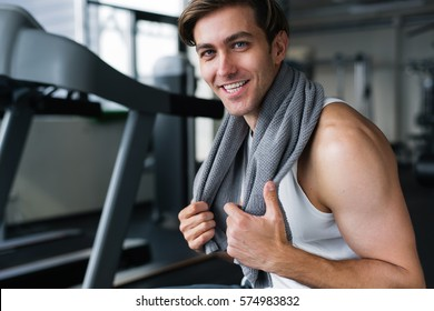 Handsome young man resting after workout with towel around his neck