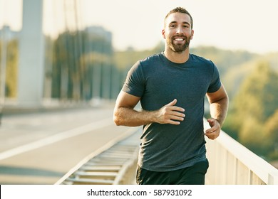 Handsome young man running across the bridge.