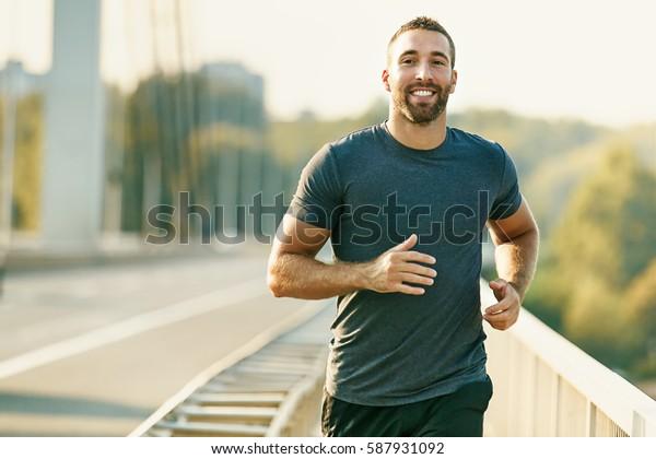 Schöner junger Mann, der über die Brücke lief.